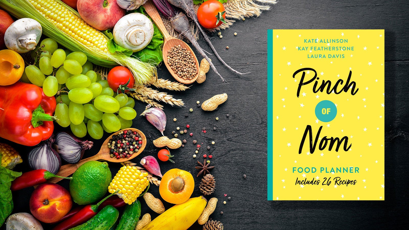 The Pinch of Nom Food Planner set on a black counter next to a pile of fruit and vegetables.