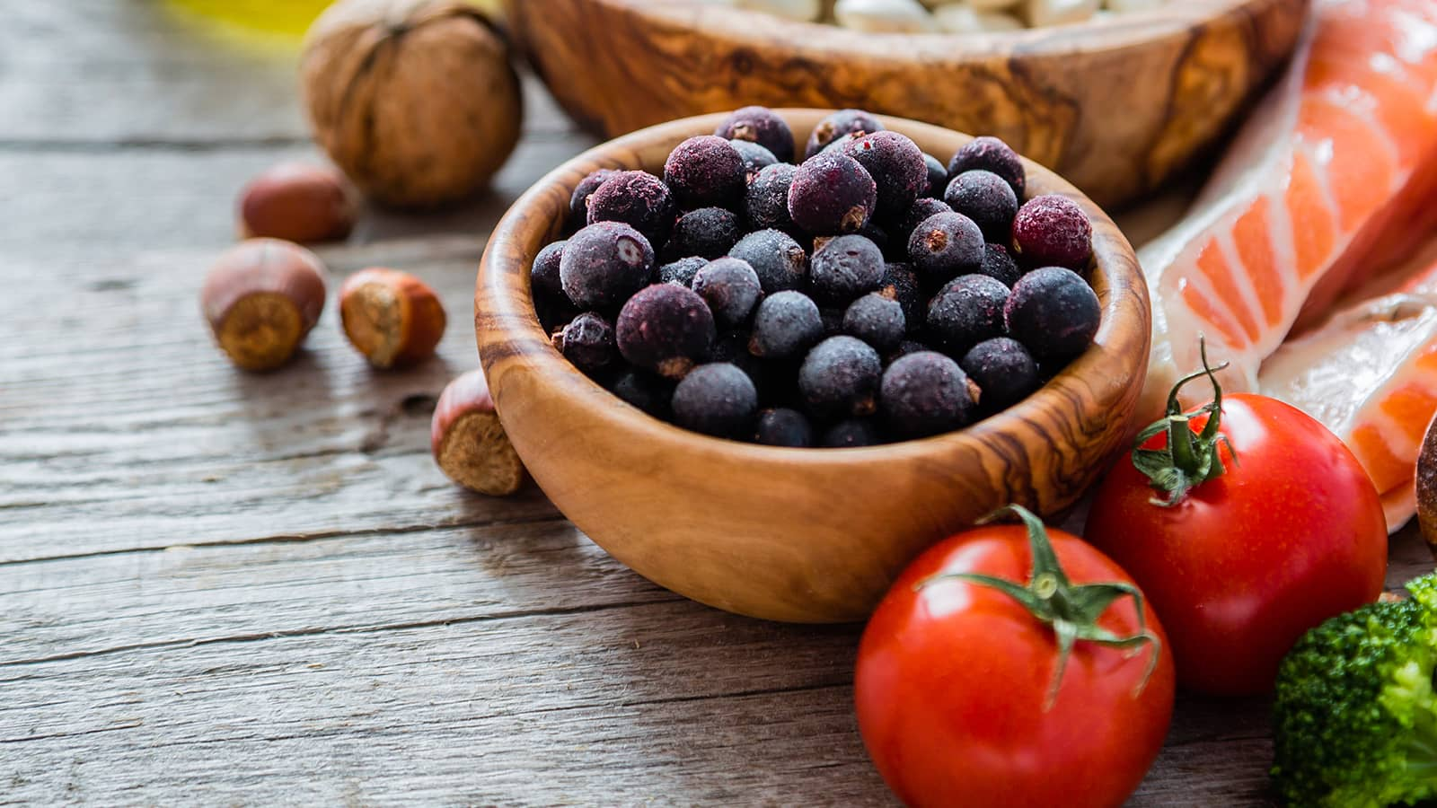 Wooden bowl of blueberries with arrangement of other healthy food - tomatoes