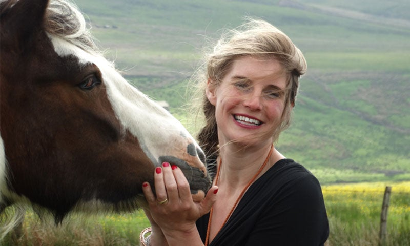 The Yorkshire Shepherdess, Amanda Owen, with a horse in a field.