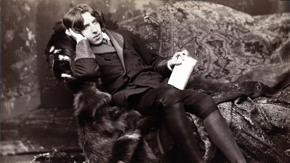 Oscar Wilde photographed sitting in a fur covered chair.