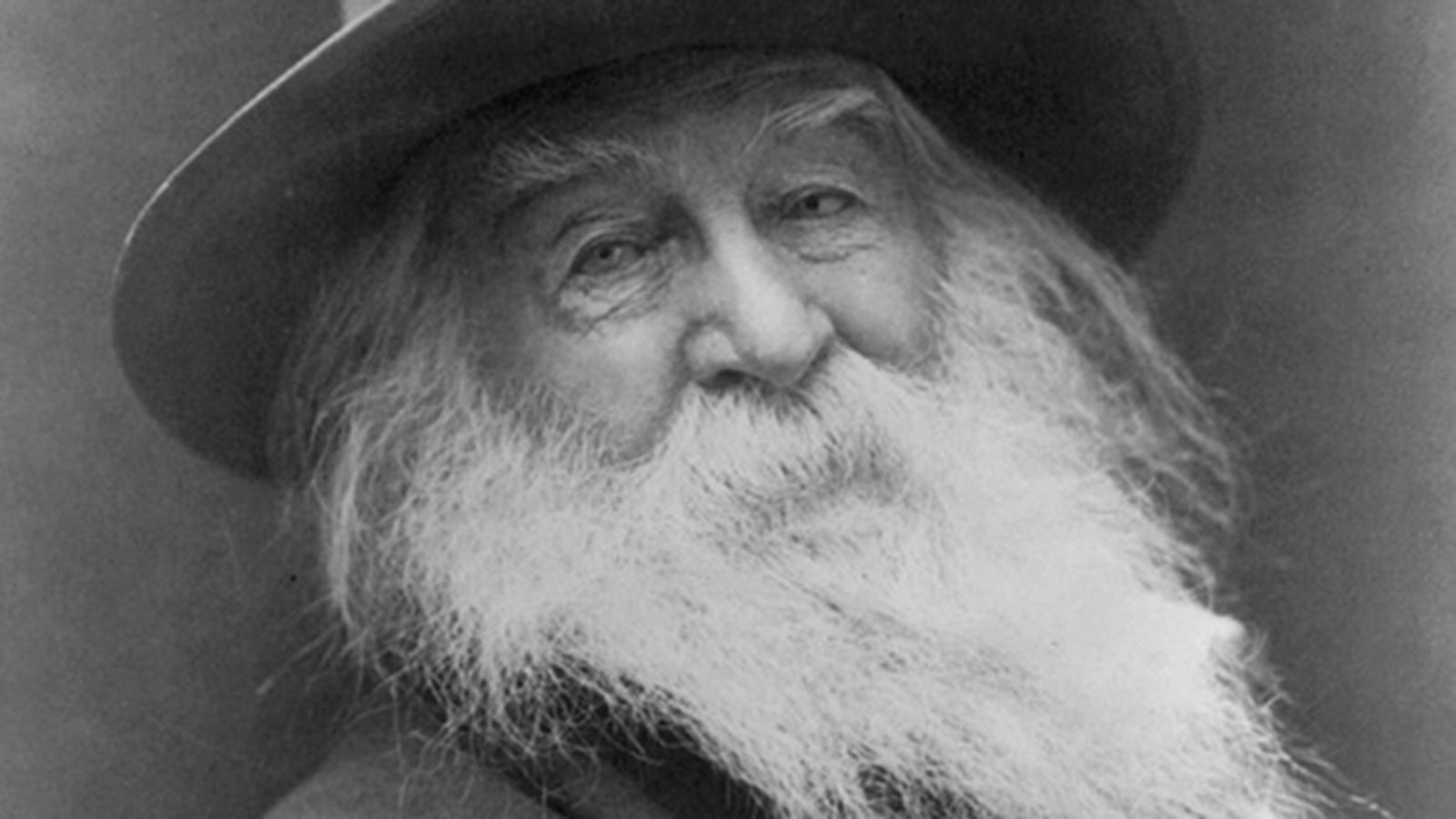 A close up black and white photograph of an elderly Walt Whitman, with a long white beard, wearing a dark wide-brimmed hat