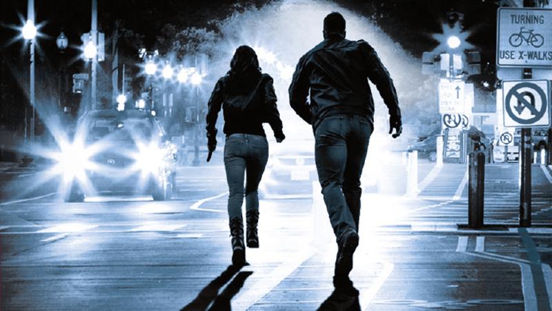 Man and woman running away down street