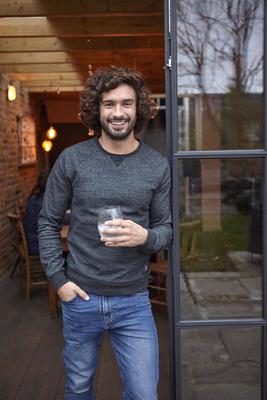 A photo of Joe Wicks holding a glass