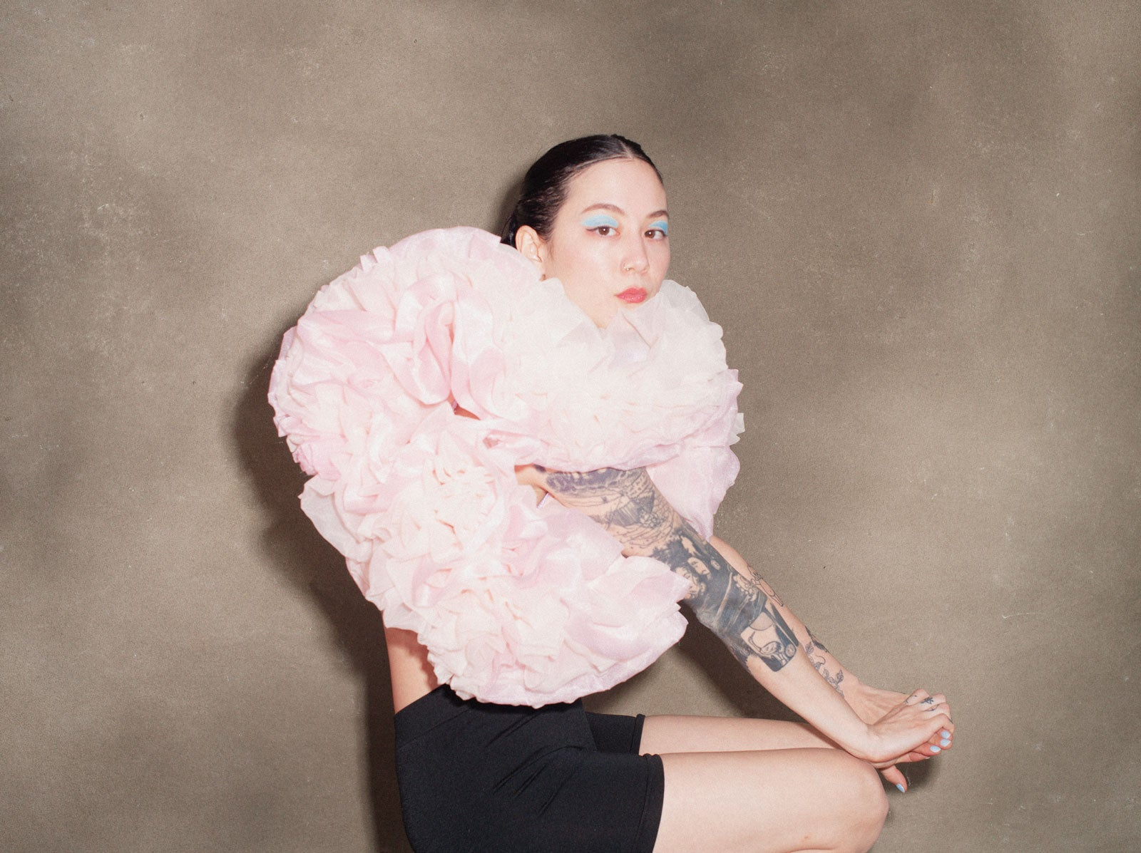 Michelle Zauner sitting sideways on a stool, wearing an oversized pink ruffled top, black shorts and bright blue eye shadow