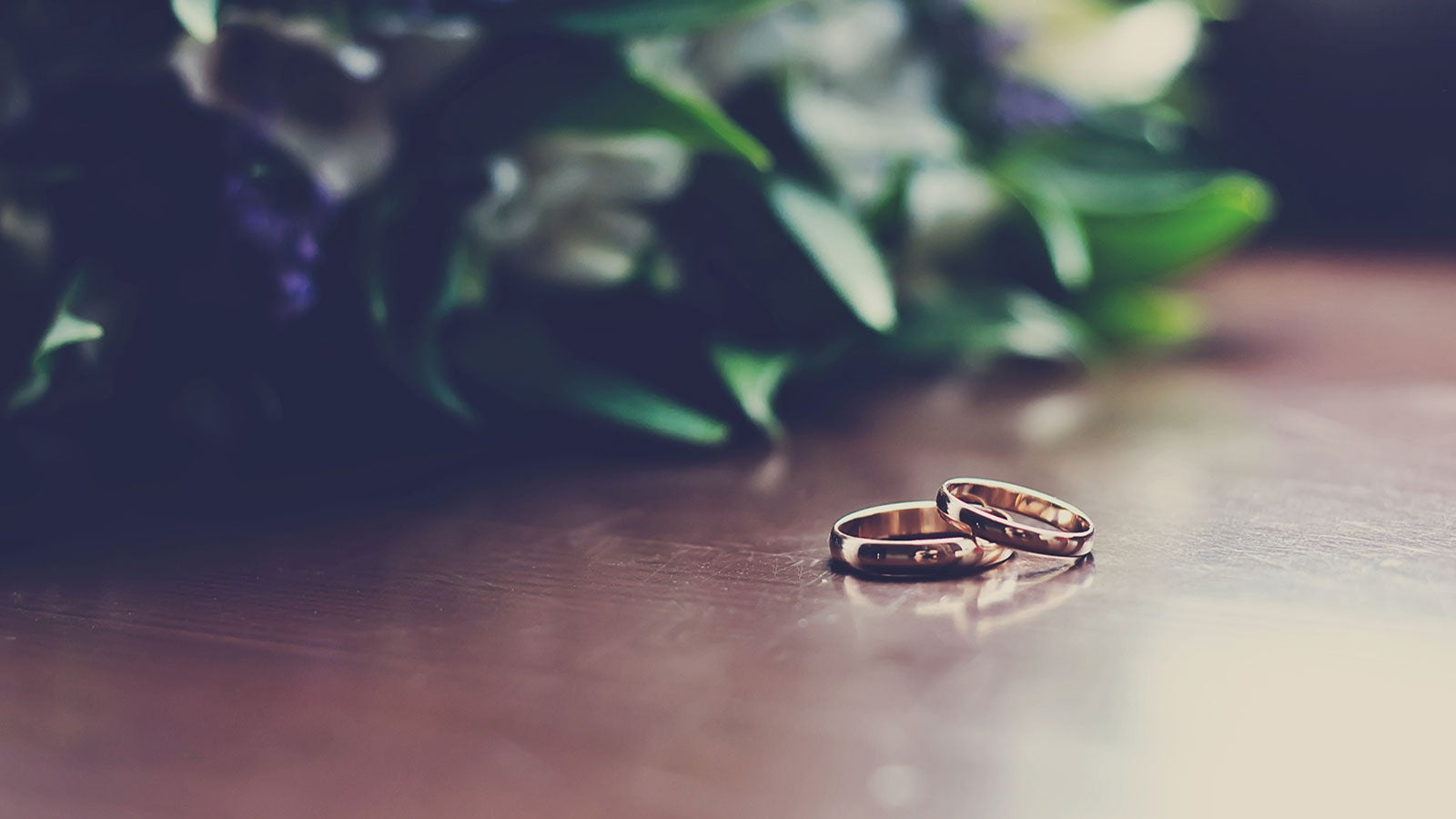 Two gold wedding bands rest on a wooden table in front of a bouquet.