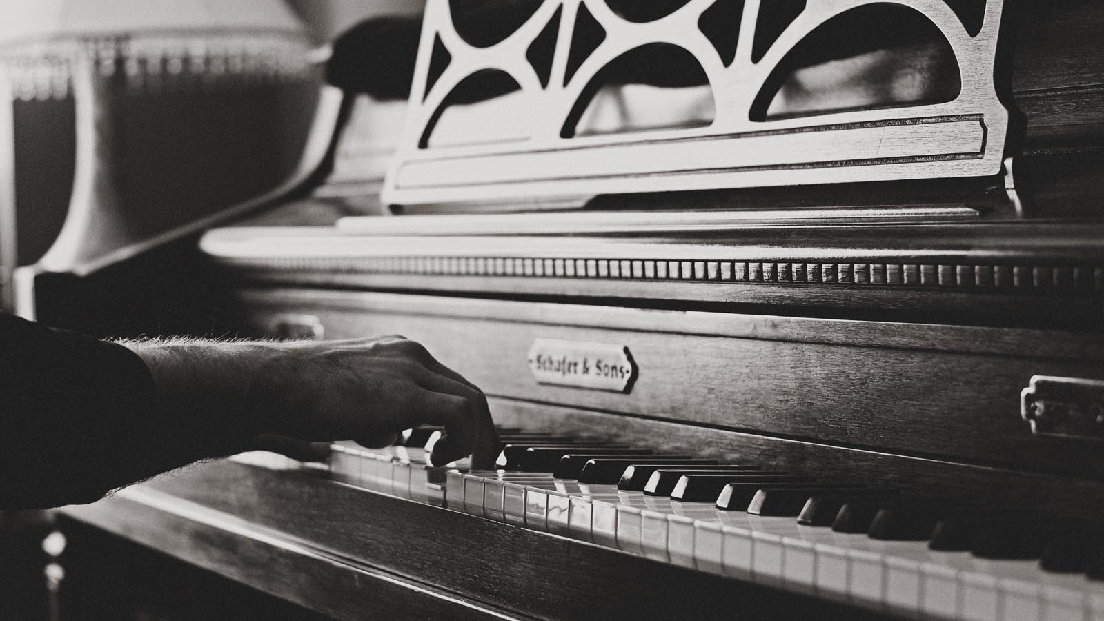Hands playing piano black and white