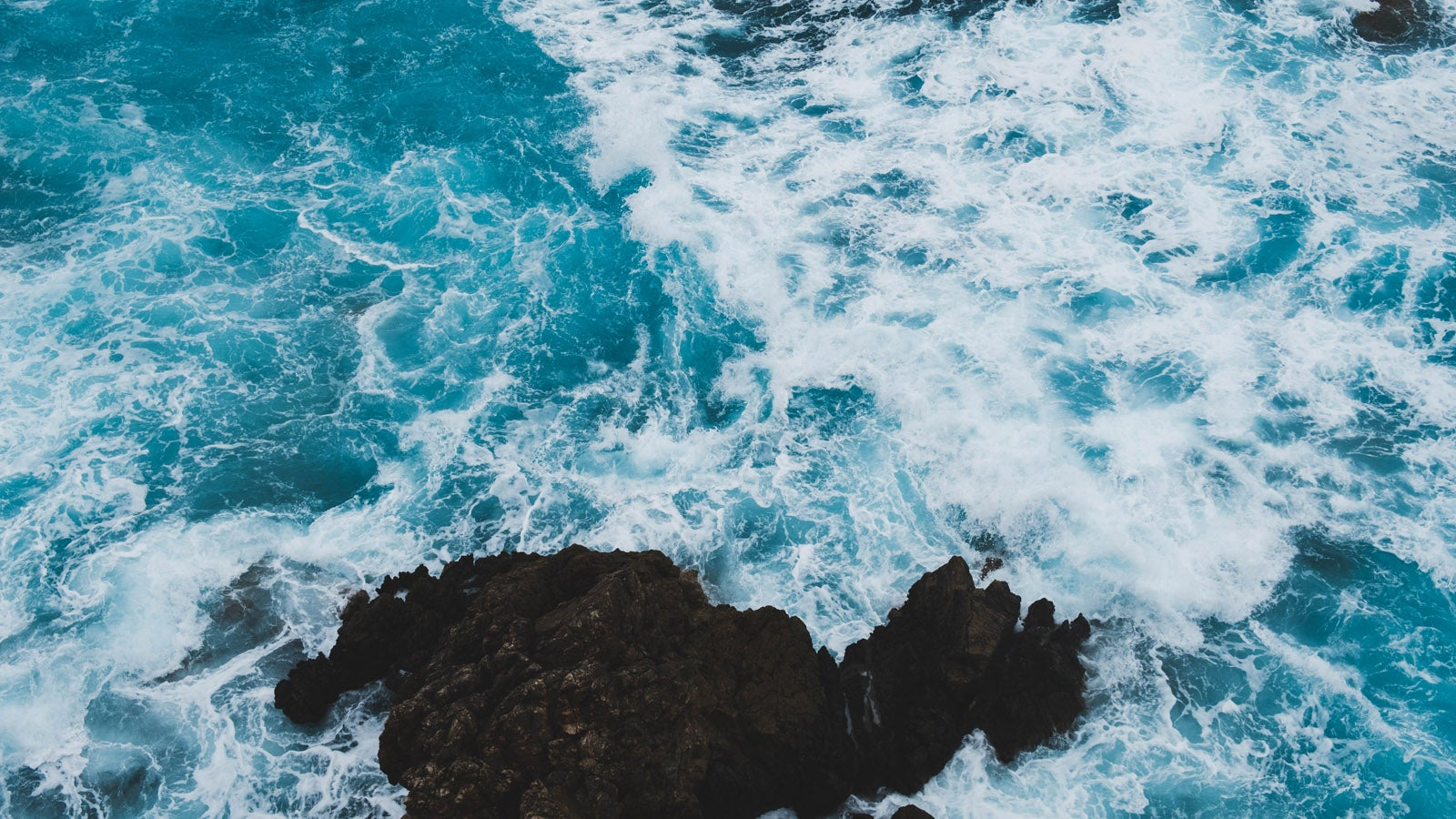 A photo of waves crashing against a rocky outcrop