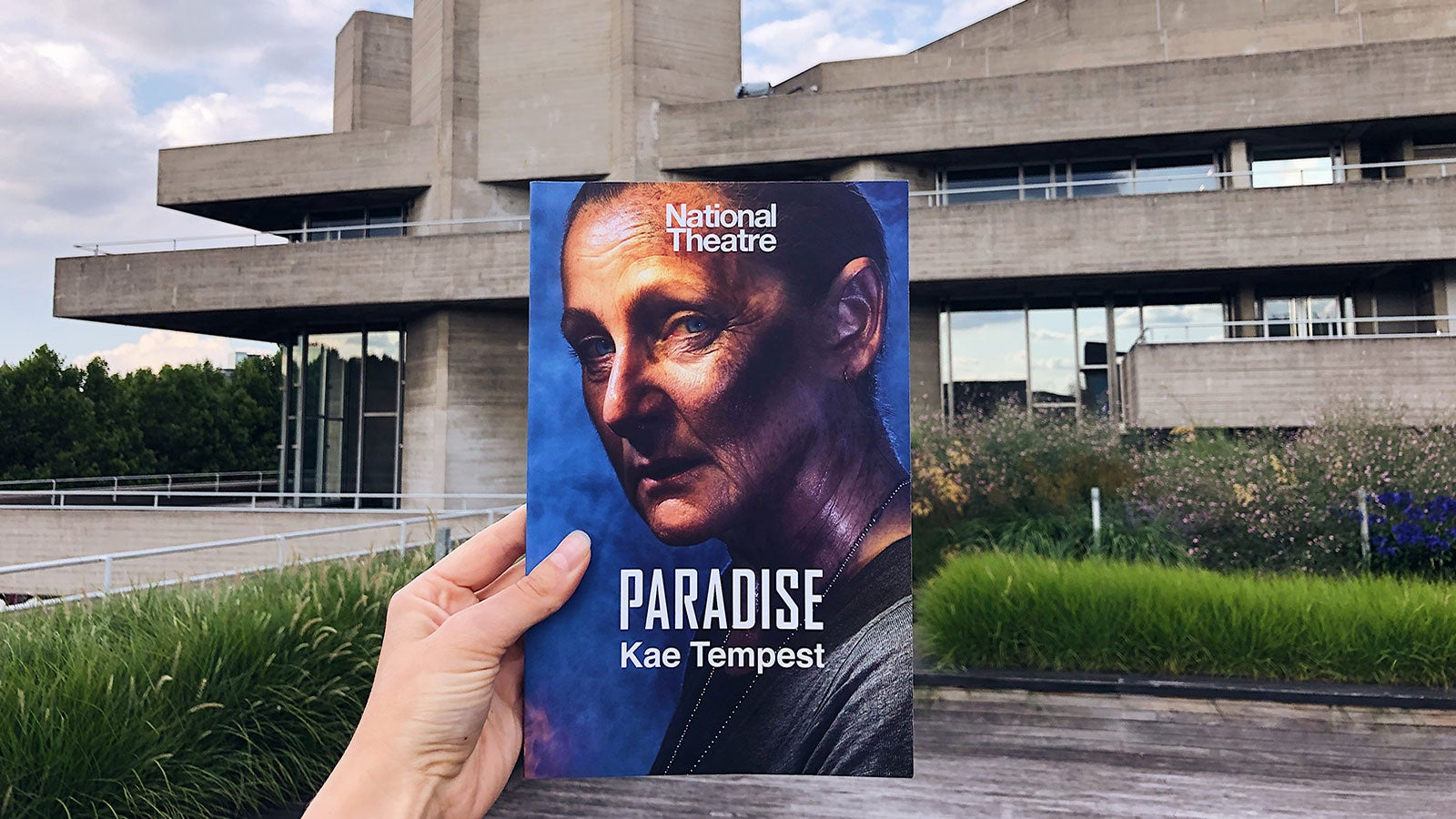 Someone holds a copy of Kae Tempest's Paradise up against the backdrop of London's iconic National Theatre building.