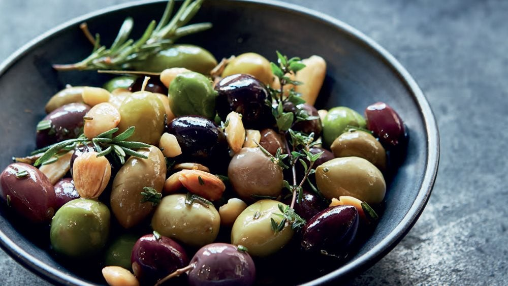 Warm Herbed Olives with Marcona Almonds in a bowl