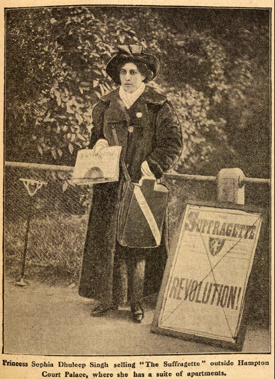 Sophia Duleep Singh standing next to a sign that says 'SUFFRAGETTE REVOLUTION' holding informational papers on the suffragette movement to hand out to the public
