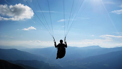 Silhouette of person in parachute against background of mountains and blue sky
