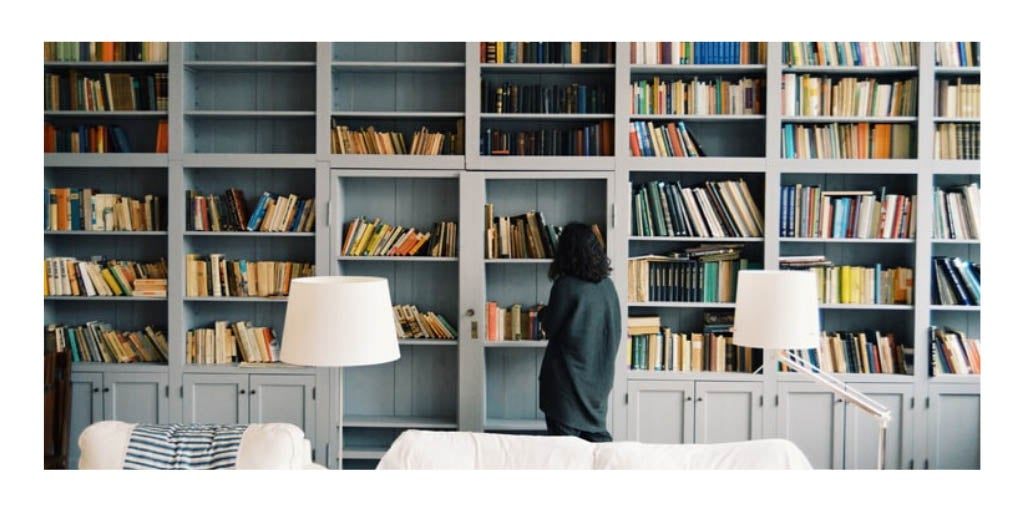 Photo of a lady browsing books on a wall to wall bookshelf