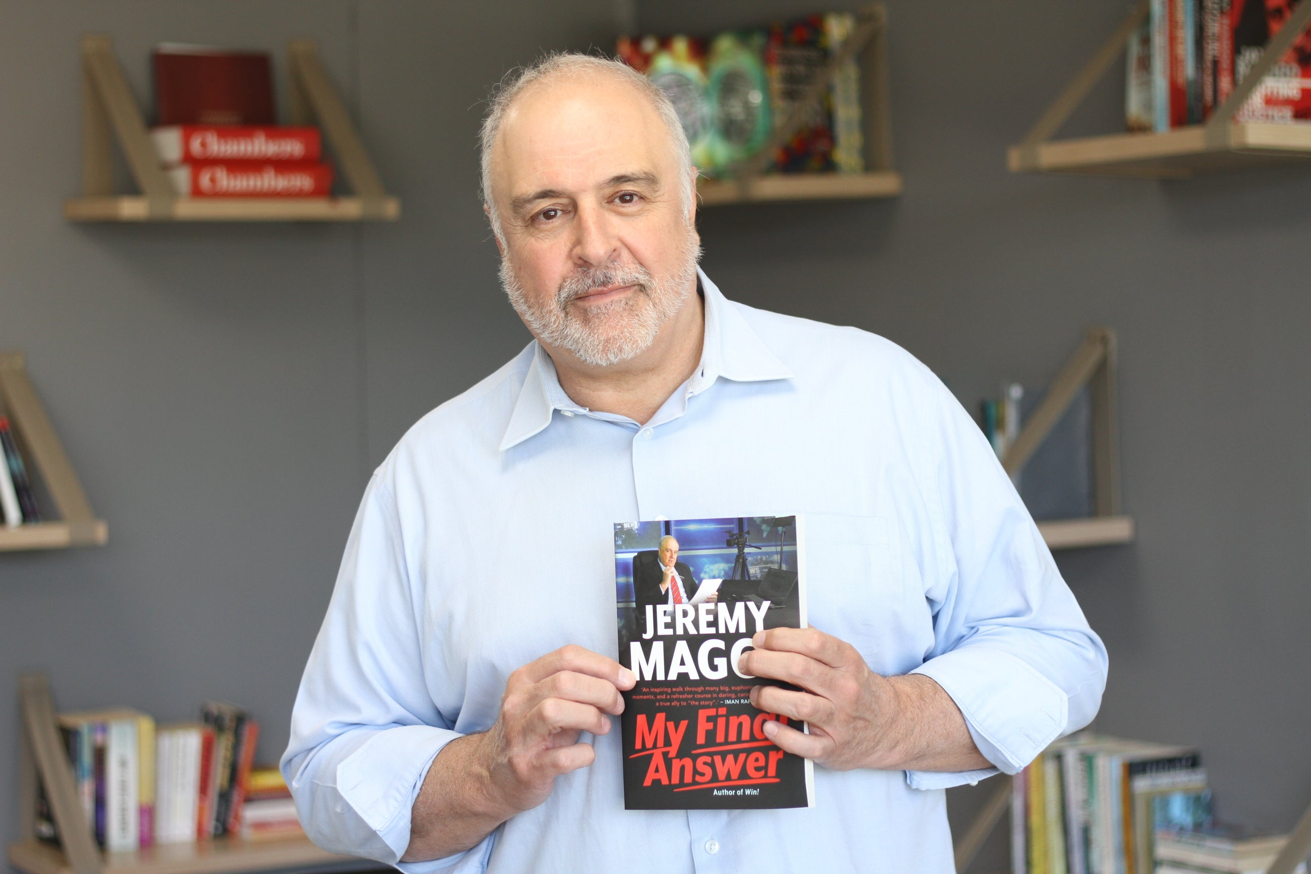 A photo of Jeremy Maggs in a blue shirt, holding a copy of his book 'Final Answer'