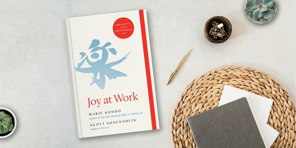 Photo of a desk with Joy at Work by Marie Kondo on it and a pen and notebook