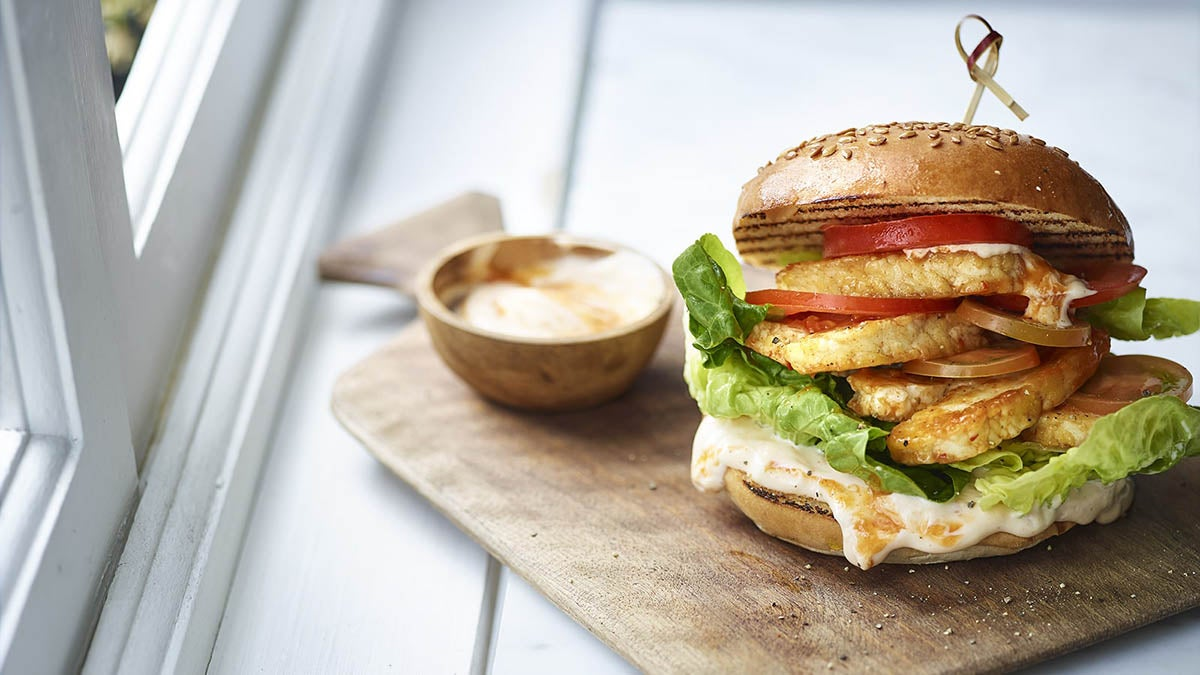 A photo of a Halloumi Burger on a bread board with a side bowl of dip
