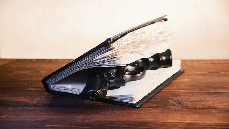 A photo of a gun between pages of a book on a wooden desk
