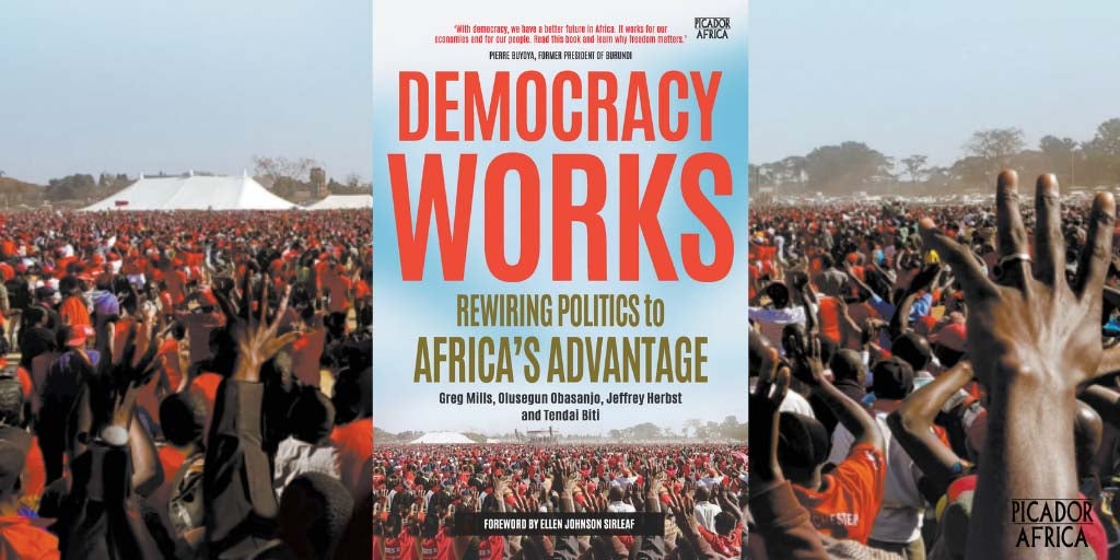 Photo of the book Democracy Works superimposed on a photo at a political gathering with hundreds of people with their hands in the air.