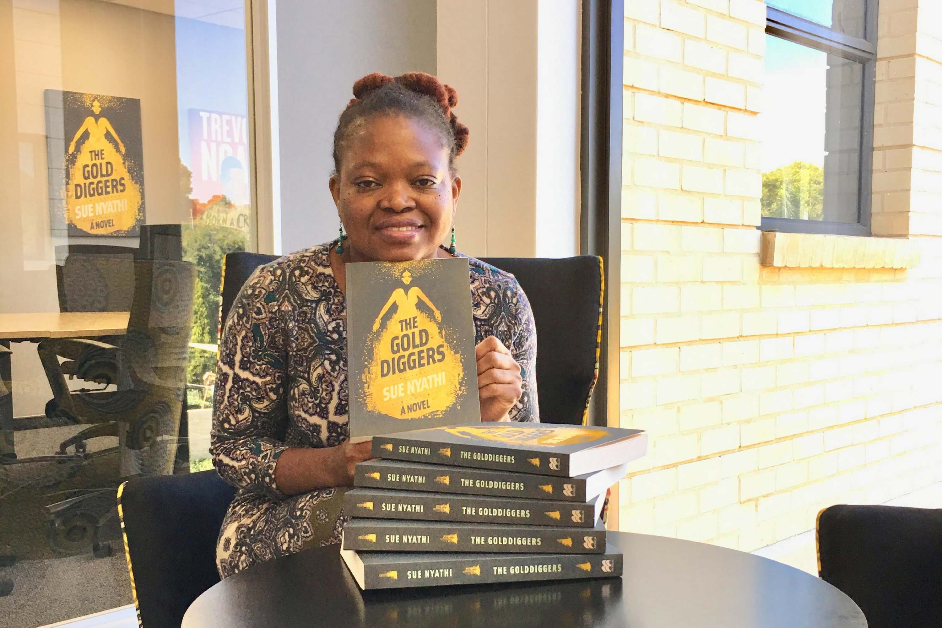Photo of Sue Nyathi sat a table with copies of her book the The Gold diggers