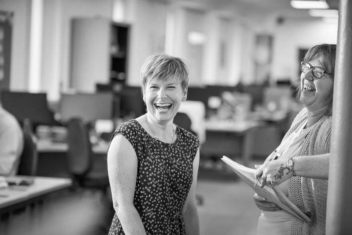Two colleagues laughing together in an office
