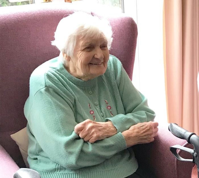 Resident, June, sitting in an armchair in her home