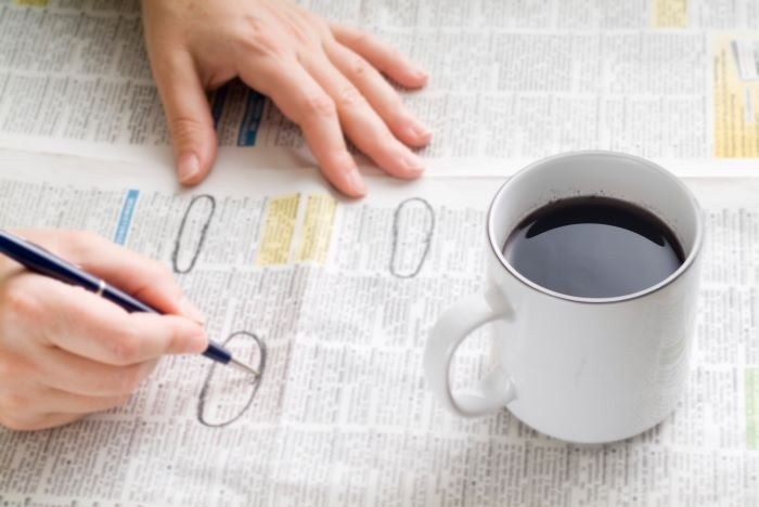 A close up of someone circling job ads in the paper with a cup of coffee