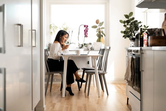 Woman working from home at her kitchen table