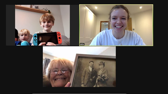 A zoom meeting with two younger people and an older person holding up their posessions