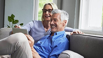 An older couple sitting on a sofa looking at an iPad.