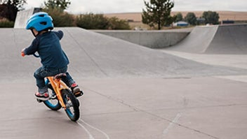 A young child riding a bicycle around a skatepark