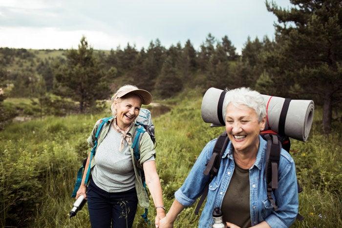 An older couple hiking through a field