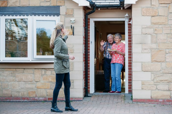 A woman waving to an older couple in the doorway of their home