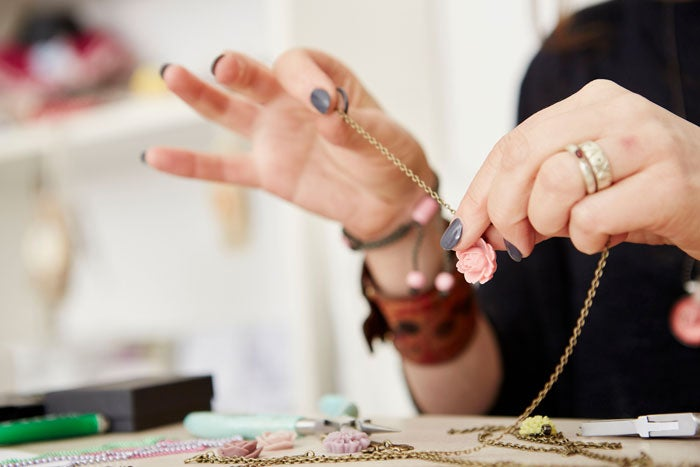 Close up image of hands making a necklace