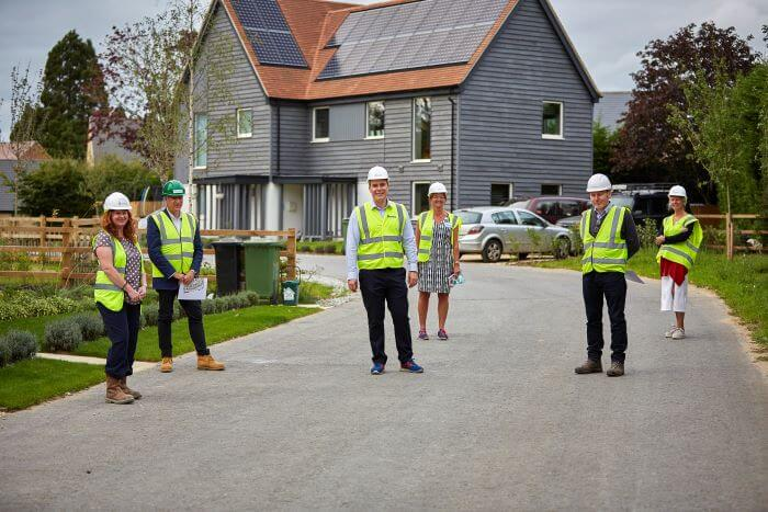 MP David Johnston stands in front of new carbon-zero homes near Abingdon