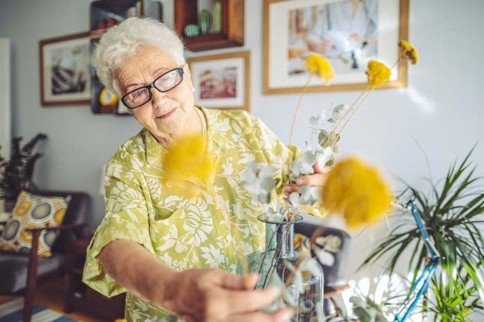 Lady arranging flowers in her home