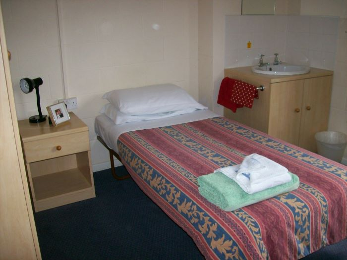 single bed with wash basin and bedside table