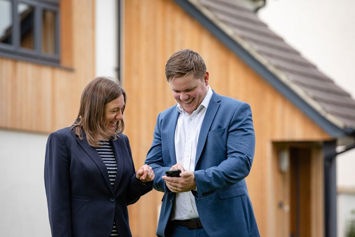 Two colleagues looking at information on a mobile phone