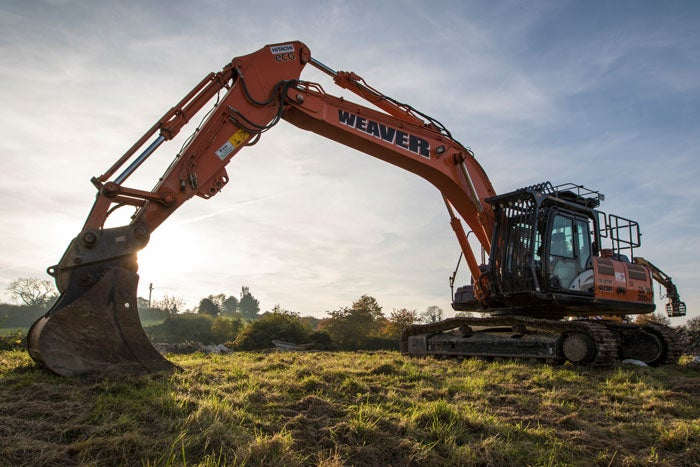A large digger breaking ground in a field