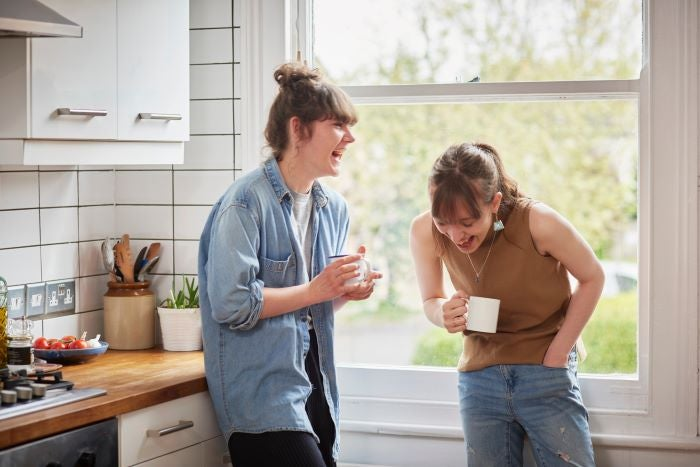 2 young woman laughing in a kitchen