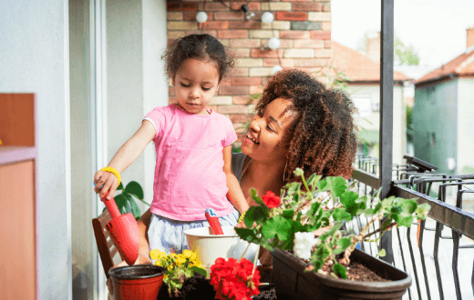 Mother and daughter on a balcony planting in pots