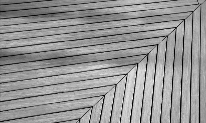 Black and white image of decking planks meeting to an arrow in the top right corner