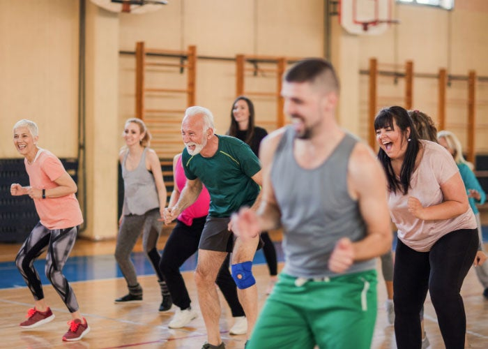A group of people in a community exercise group in a PE hall