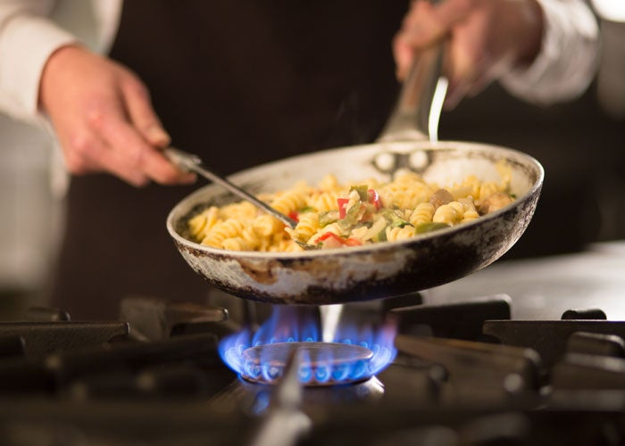A close up of a pan of food being cooked over a gas flame