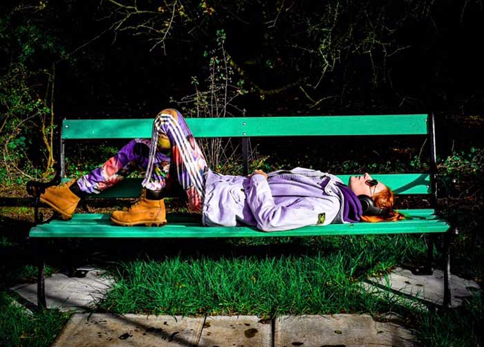A young person lying on a bench listening to music