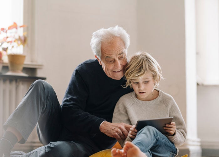A grandfather and child looking at a tablet together