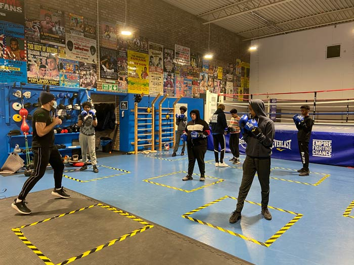 A group of teenagers attending a boxing class in a boxing gym