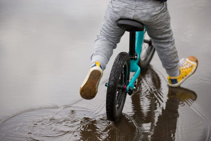 Young child on a bike riding through a puddle