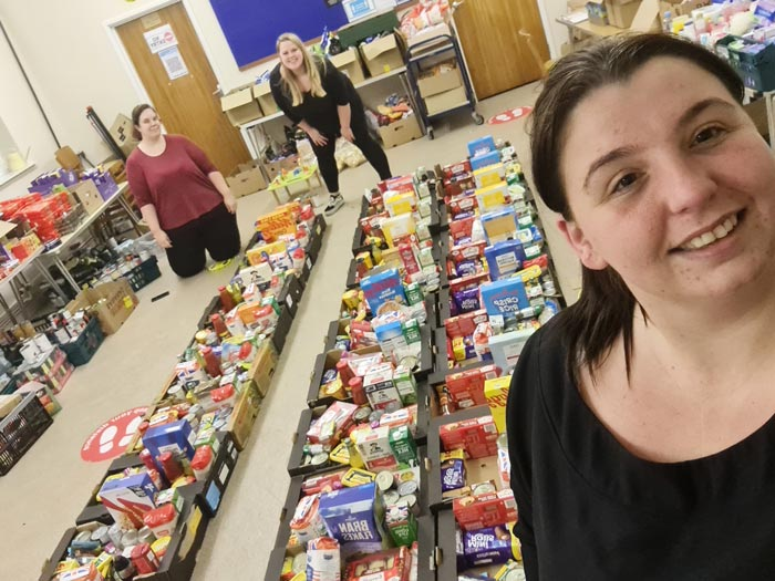 a team of people standing with rows of food boxes prepared for distribution in Bristol