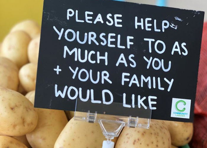 Close up image of a box of potatoes with a sign in them saying 'Please help yourself to as much as you and your family would like'