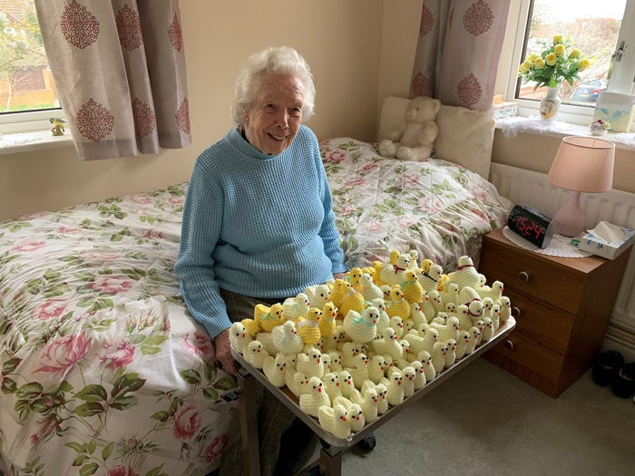 Resident, Muriel, sitting with a tray of knitted chicks