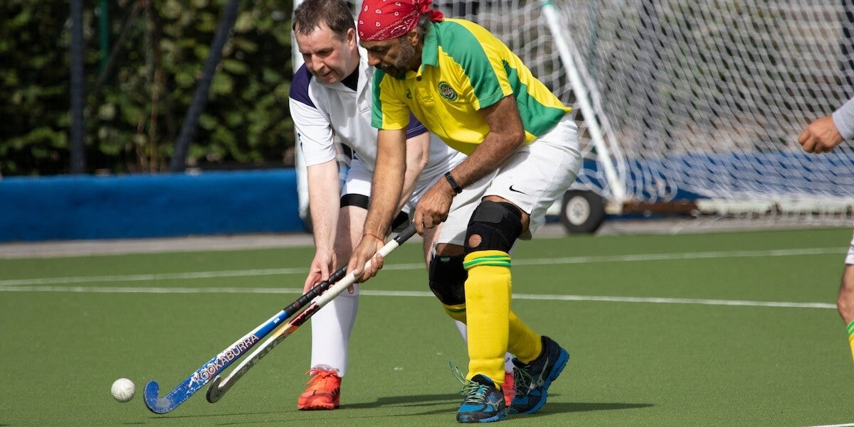 Adult males playing hockey at the England Hockey Championships